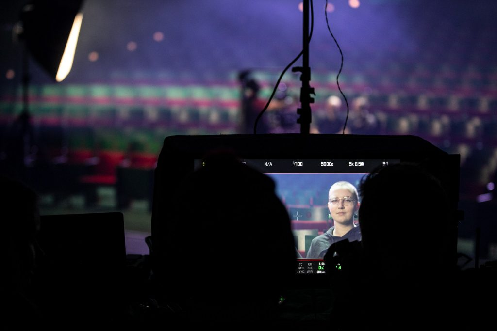 Na zdjęciu widoczny ekran na którym wyświetla się twarz kobiety. W oddali widać pustą widownię.