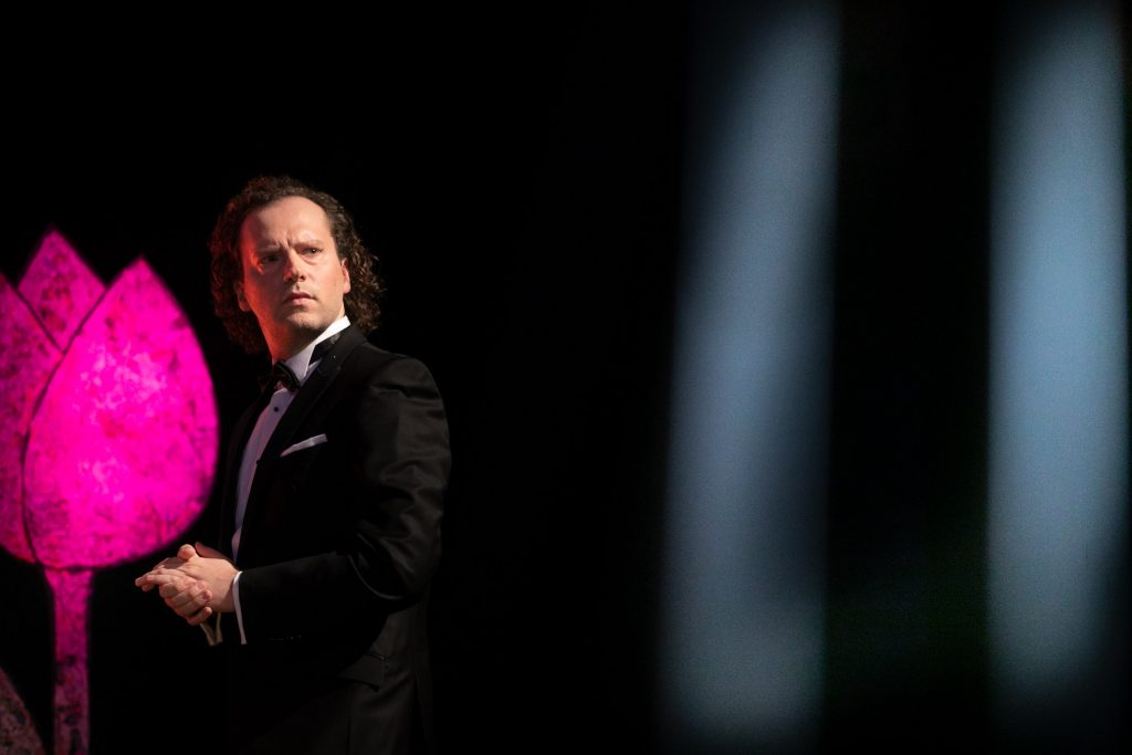 Mężczyzna w czarnym garniturze stoi z głowa skierowaną w bok. Przed nim po lewej stronie widoczny różowy tulipan.