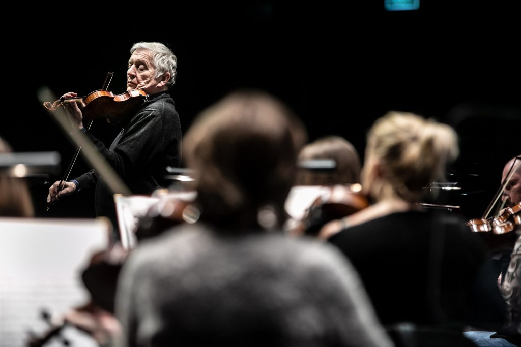 Zbliżenie na solistę podczas próby do koncertu. Przed nim siedzi orkiestra.