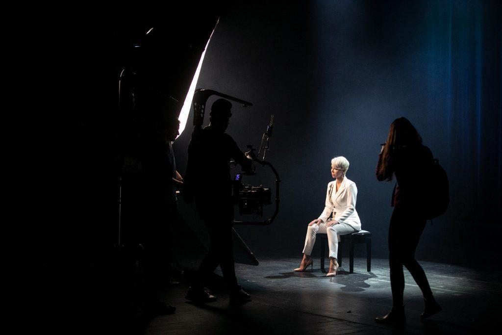 Na środku siedzi kobieta w białym garniturze. Przed nią stoi mężczyzna z kamerą. Za nim widać parasol zdjęciowy. Po prawej stronie stoi tyłem kobieta z plecakiem.
