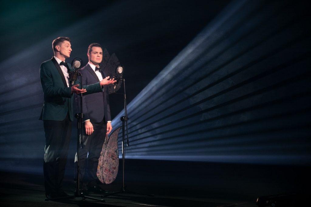 Na czarnym tle stoi dwóch mężczyzn w garniturach. Za nimi wyłaniają się jasne smugi światła.