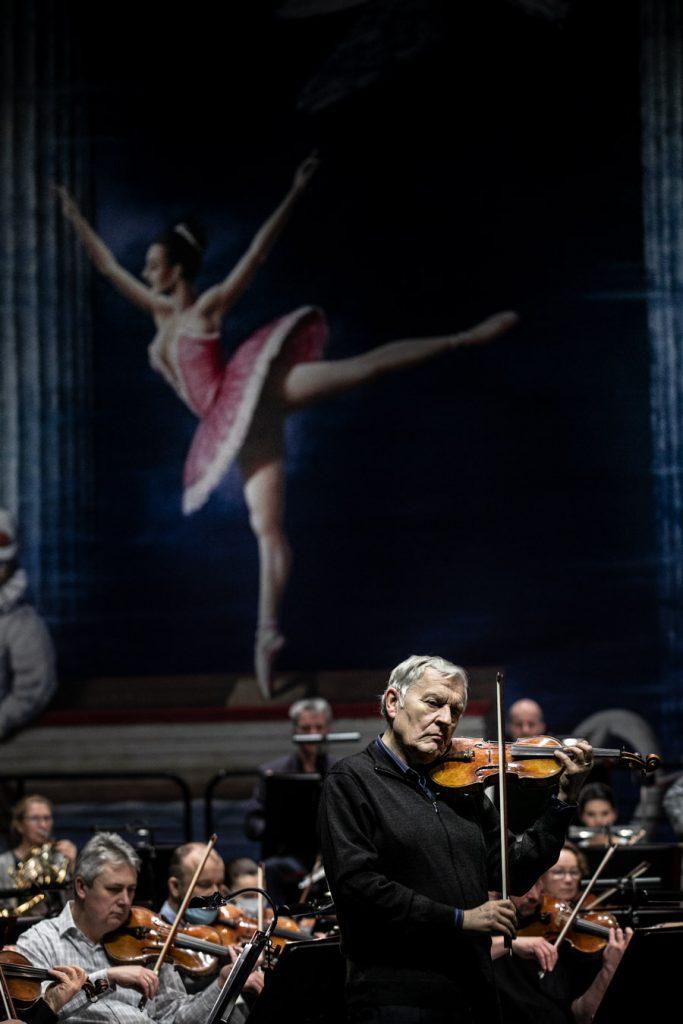 Na środku stoi solista grający na skrzypcach. Za nim siedzi orkiestra.