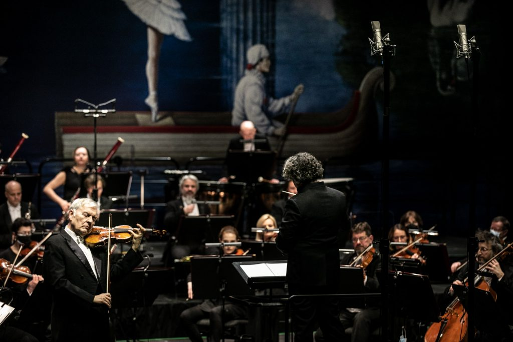 Na środku na podeście stoi tyłem dyrygent. Po lewej stronie solista grający na skrzypcach. Za nim siedzi orkiestra.