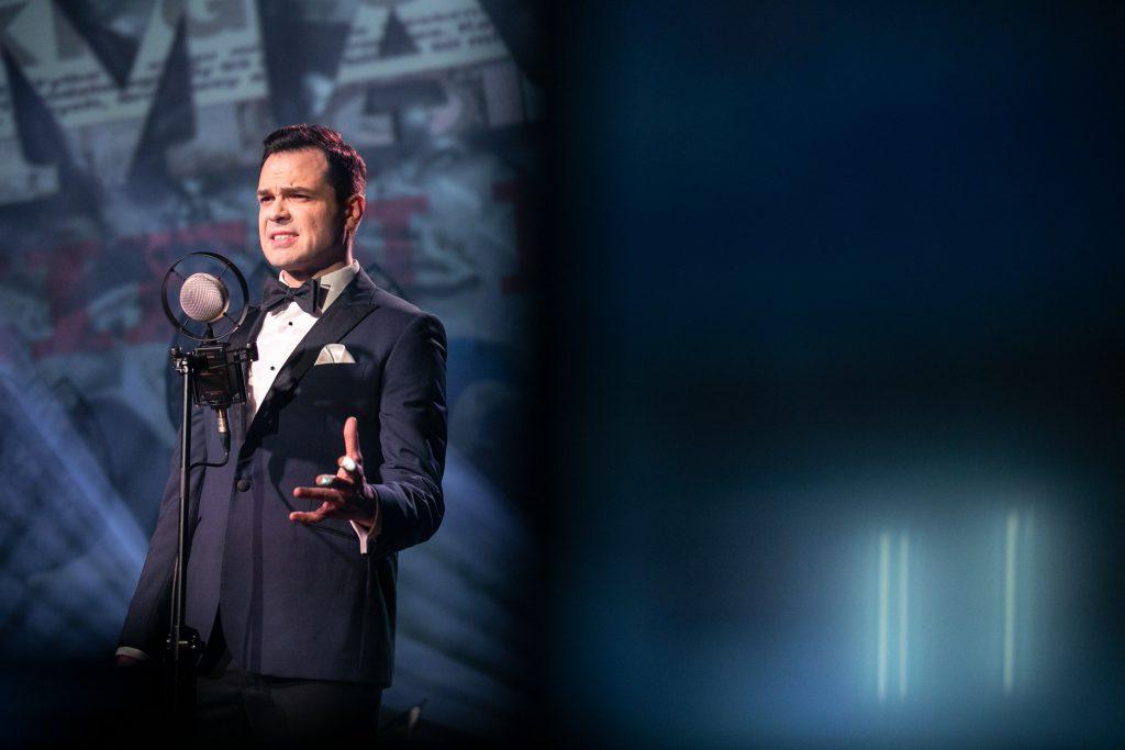 Mężczyzna w garniturze stoi przed mikrofonem na statywie. Jedną rękę ma uniesioną do boku. Patrzy przed siebie.