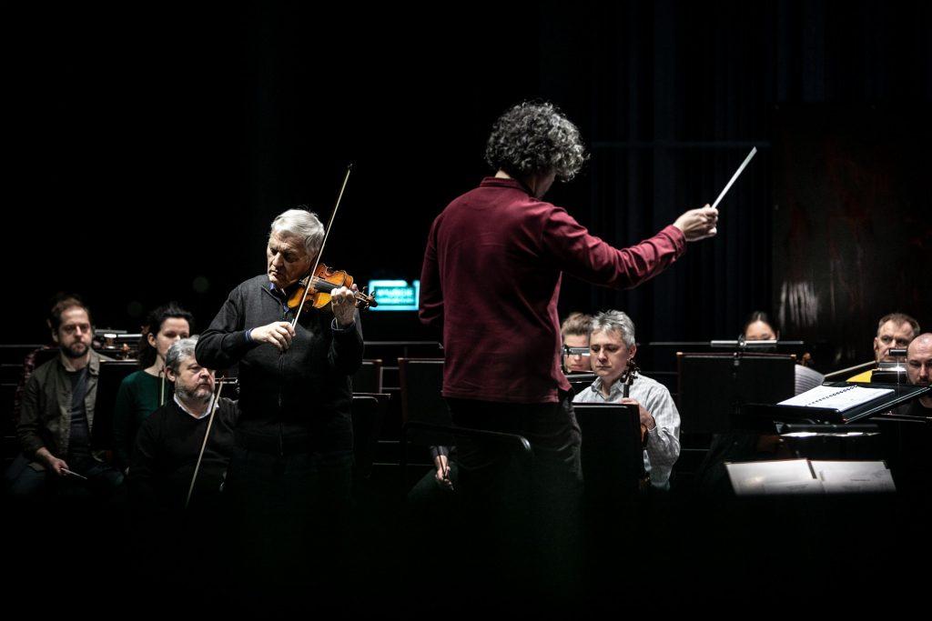 Na środku na podeście stoi dyrygent. Po lewej stronie solista gra na skrzypcach. Za nimi siedzi orkiestra.
