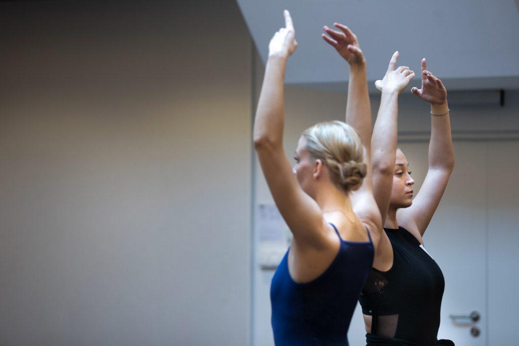Dwie kobiety z uniesionymi rękoma do góry stoją tyłem do siebie.