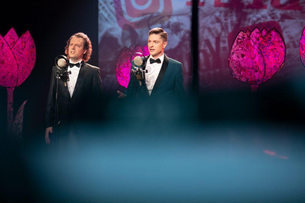 Dwóch mężczyzn w garniturach stoi przy mikrofonach patrząc przed siebie. Za nimi widoczna iluminacja świetlna w postaci różowych tulipanów.