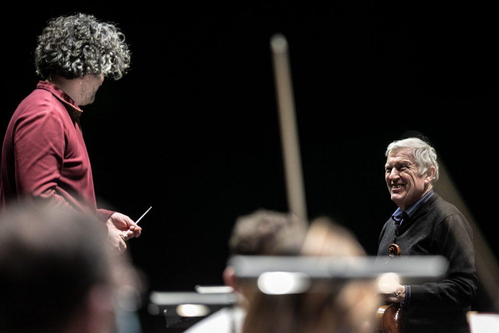 Po prawej stronie stoi uśmiechnięty solista patrząc w stronę dyrygenta.