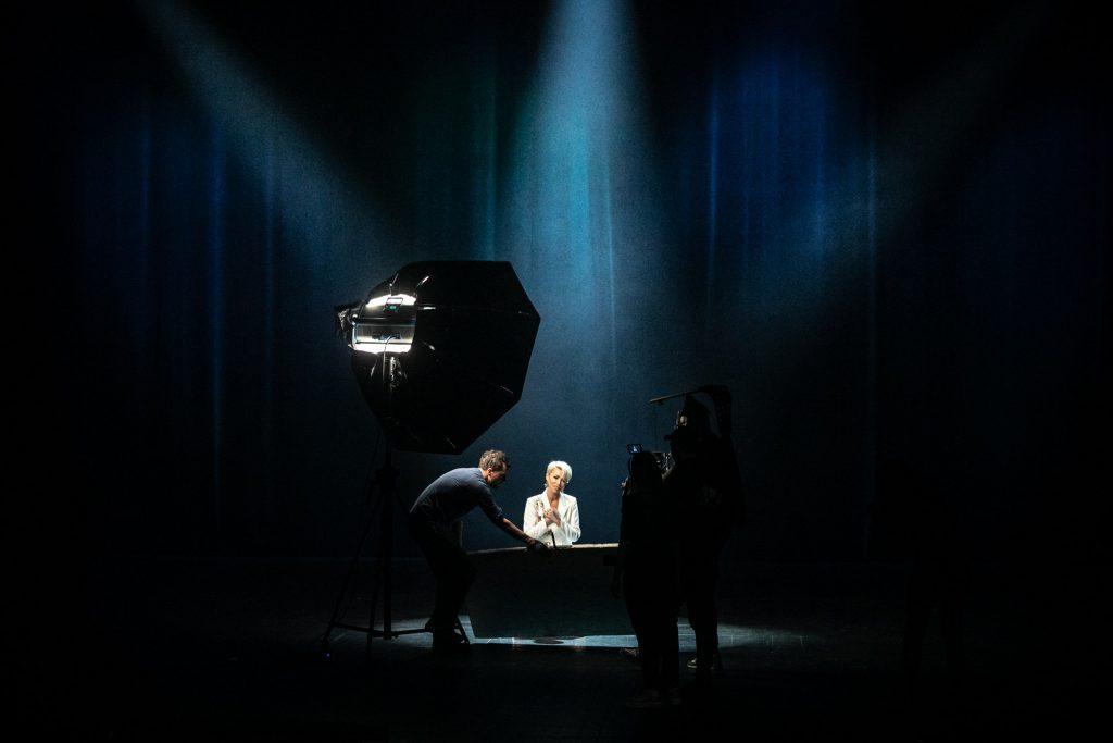 Na czarnym tle siedzi kobieta w białym garniturze oświetlona łunami jasnego światła. Przed nią stoi mężczyzna z kamerą. Po lewej stronie stoi parasol zdjęciowy.