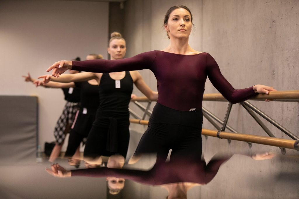 Kilka kobiet stoi przy drążku w pozycji baletowej.
