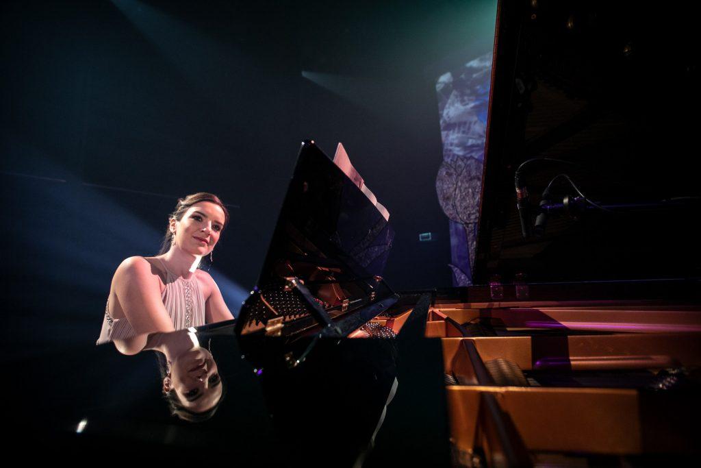 Przy fortepianie siedzi kobieta patrząca w bok.