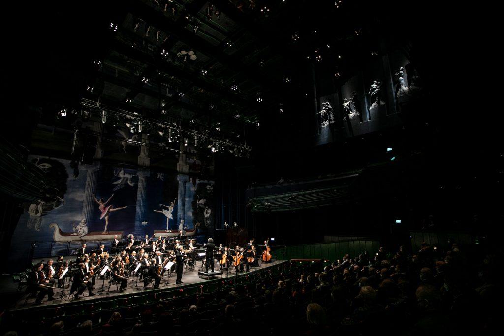 Widok z boku. Po prawej stronie widownia wypełniona publicznością. Po lewej stronie na scenie orkiestra wraz z dyrygentem podczas koncertu.