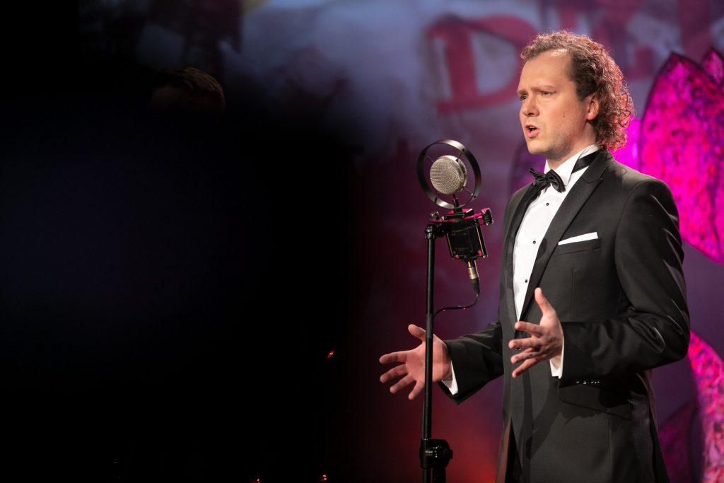 Przed mikrofonem na statywie stoi mężczyzna elegancko ubrany. Ręce ma uniesione w bok.
