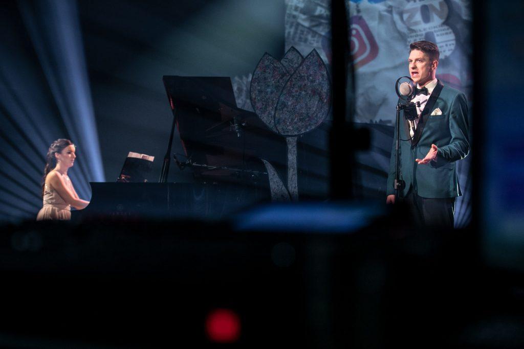 Po prawej stronie przed mikrofonem stoi mężczyzna. Po lewej stronie siedzi kobieta przy fortepianie.