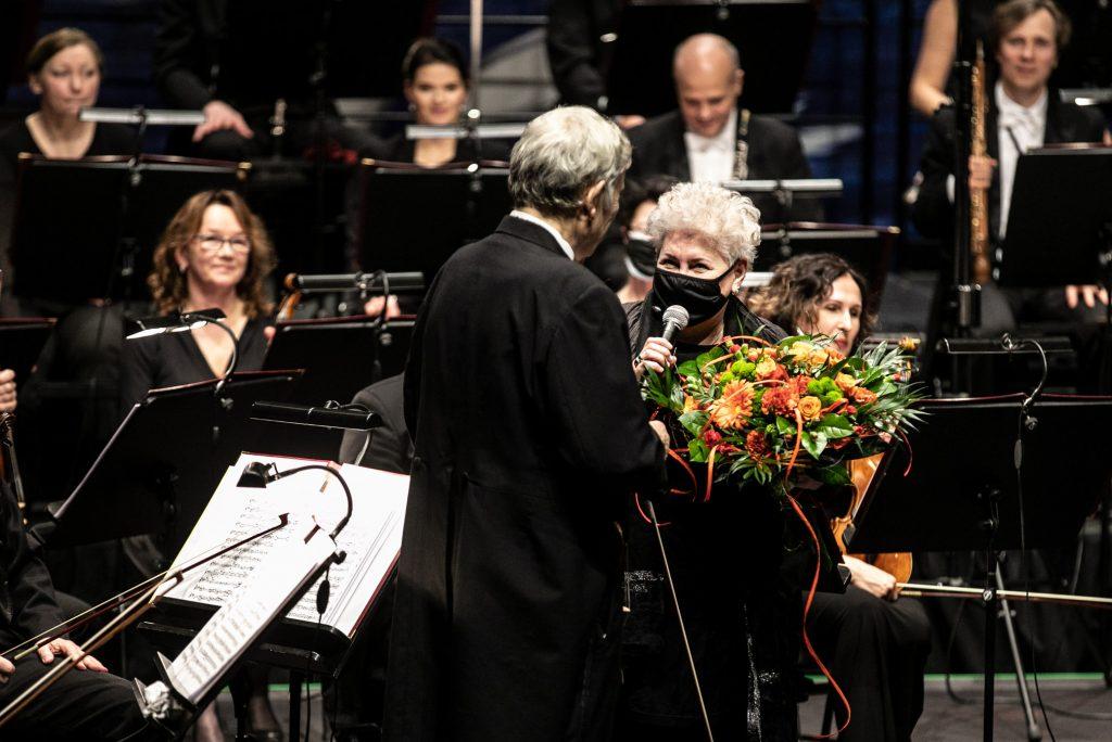 Na środku Dyrektor Prof. Violetta Bielecka z mikrofonem wręcza kwiaty soliście koncertu. Za nimi siedzi orkiestra.