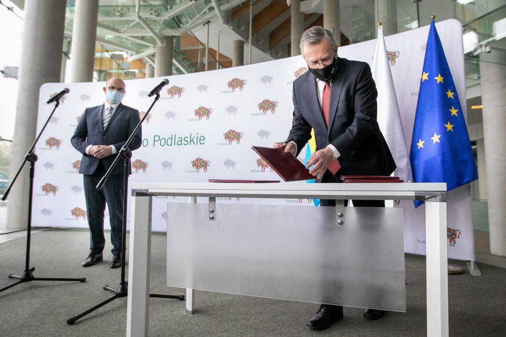 Przy białym stole stoi minister kultury i dziedzictwa narodowego prof. Piotr Gliński. W ręku trzyma bordową oprawę. Dalej po lewej stronie stoi Pan Artur Kosicki, Marszałek Województwa Podlaskiego.