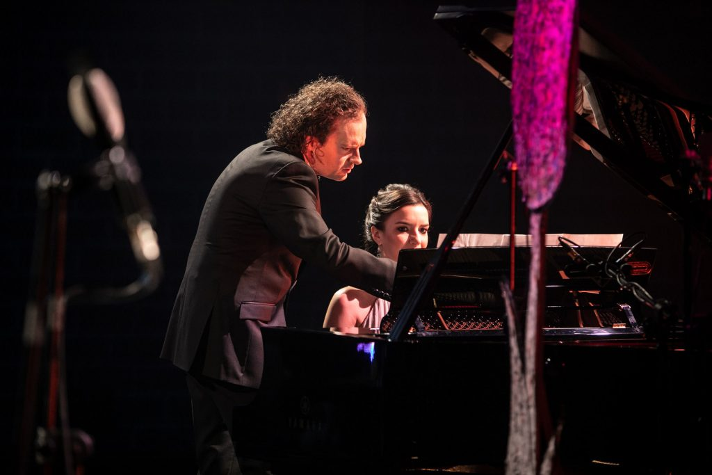 Przy fortepianie siedzi kobieta. Obok niej stoi mężczyzna w garniturze.
