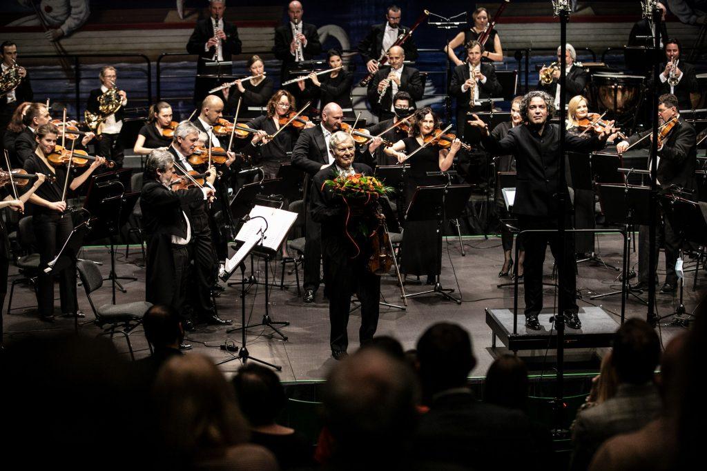 Na środku stoi solista z bukietem kwiatów. Po lewej stronie stoi dyrygent z rękoma uniesionymi w bok. Za nimi stoi orkiestra.