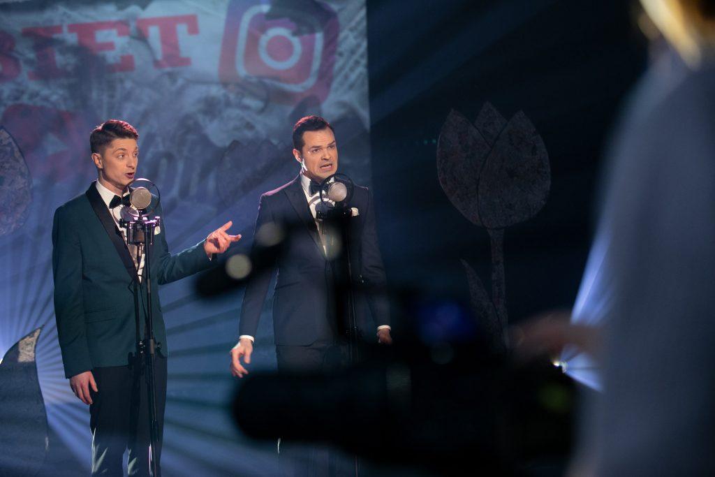 Dwóch mężczyzn stoi na scenie przy mikrofonach. Za nimi iluminacja świetlna z koncertu''8 MARCA''.
