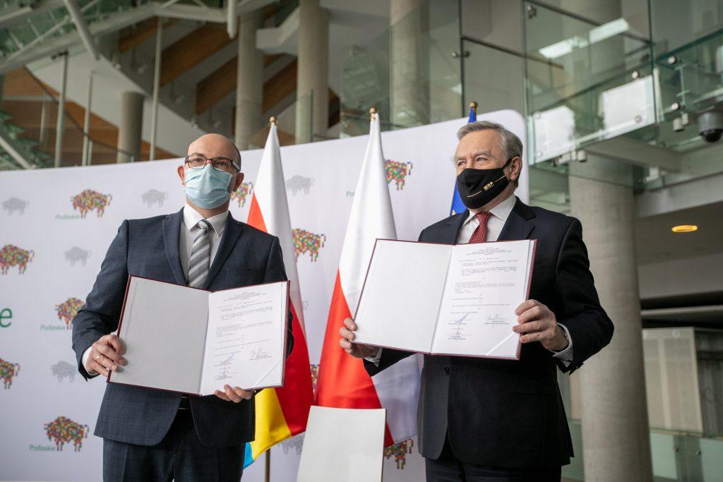 Marszałek Województwa Podlaskiego Artur Kosicki i minister kultury i dziedzictwa narodowego Prof. Piotr Gliński trzymają w rękach otwarte oprawy. W nich widoczne podpisane dokumenty.