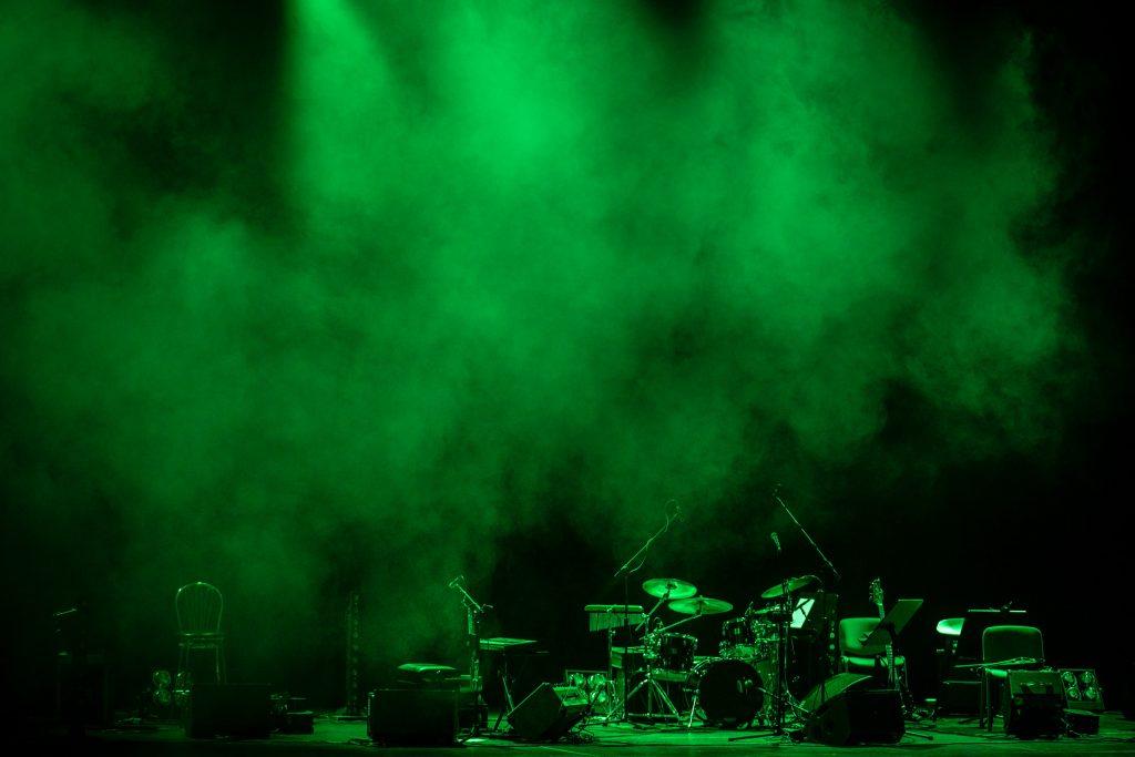 Scena w półmroku wypełniona dymem podświetlonym zielonym światłem. Na scenie stoją instrumenty muzyczne.