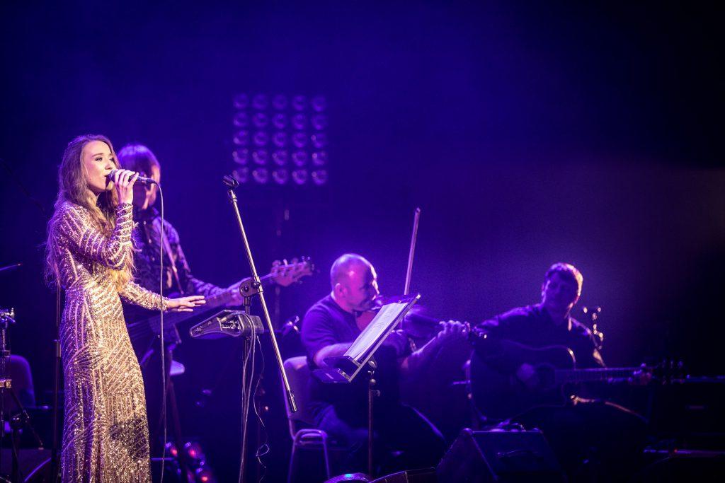 Scena w półmroku. Po lewej stronie kobieta w długiej , złotej sukni. Śpiewa trzymając mikrofon. Obok trzech mężczyzn, grających na instrumentach muzycznych.