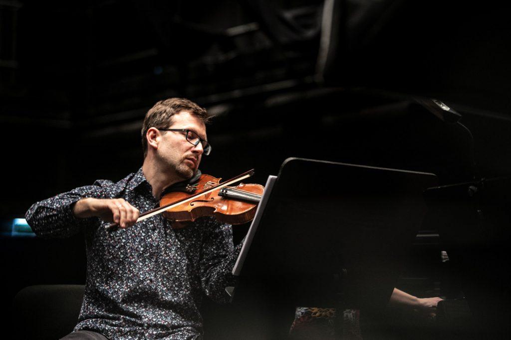 Zbliżenie na mężczyznę grającego na skrzypcach.
