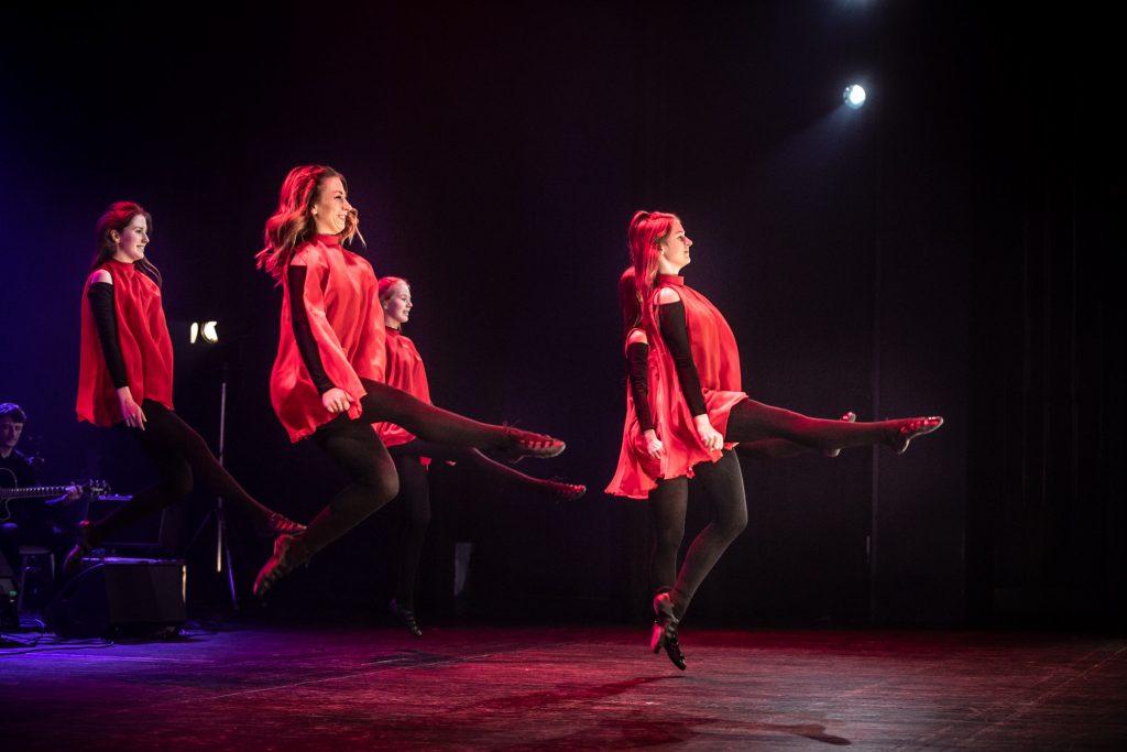 Scena w półmroku. Na niej cztery kobiety w czerwonych sukienkach. Ujęcie w podskoku, z prawymi nogami uniesionymi do przodu.