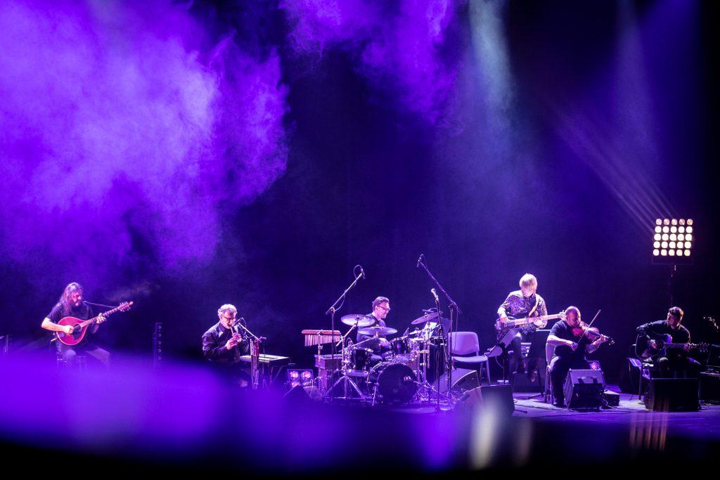 Scena oświetlona niebieskim światłem. Na niej 6-cio osobowy zespół muzyczny z instrumentami.