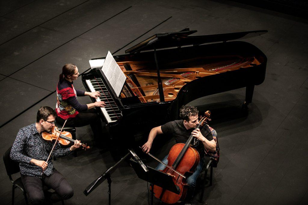 Widok z góry. Na scenie trzy osoby. Kobieta grająca na fortepianie oraz dwóch mężczyzn. Jeden grający na skrzypcach, drugi - na wiolonczeli.