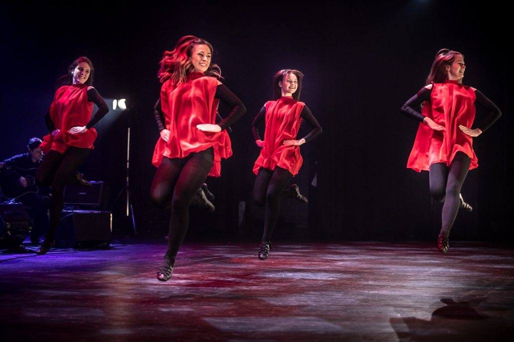 Na scenie tańczy kilka kobiet w czerwonych sukienkach. Ujęcie pozycji w podskoku z jedna nogą uniesioną do tyłu.