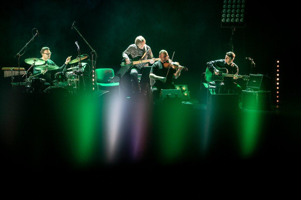 Na scenie gra zespół Carrantuohill. Z przodu widoczne smugi białego i zielonego światła.