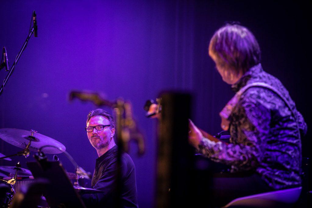 Zbliżenie na dwóch muzyków z zespołu Carrantuohill. Po prawej stronie mężczyzna grający na gitarze elektrycznej. Po lewej stronie siedzi mężczyzna przy perkusji.