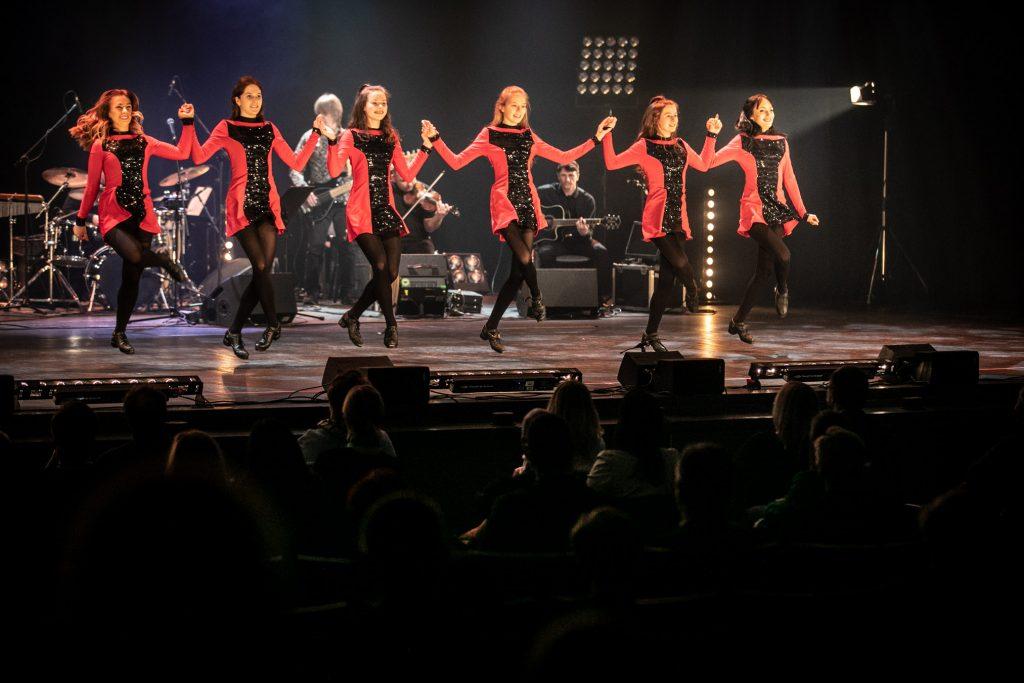 Na scenie w rzędzie tańczy kilka kobiet trzymając się za ręce uniesione do góry. Za nimi gra zespół muzyczny Carrantuohil.l