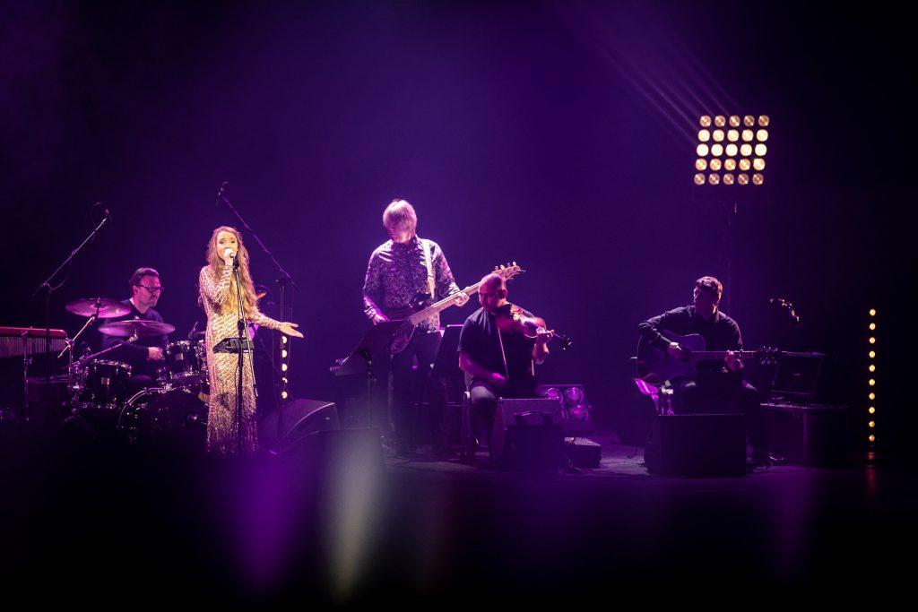 Scena w półmroku. Na niej zespół Carrantuohill podczas koncertu. Po lewej stronie przed mikrofonem stoi kobieta w długiej, złotej sukni.