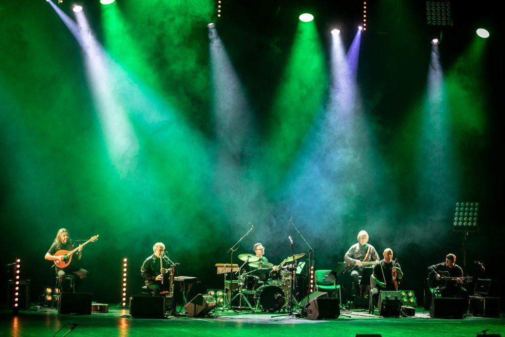 Scena oświetlona z góry smugami białego i zielonego światła. Na scenie gra 6-osobowy zespół Carrantuohill