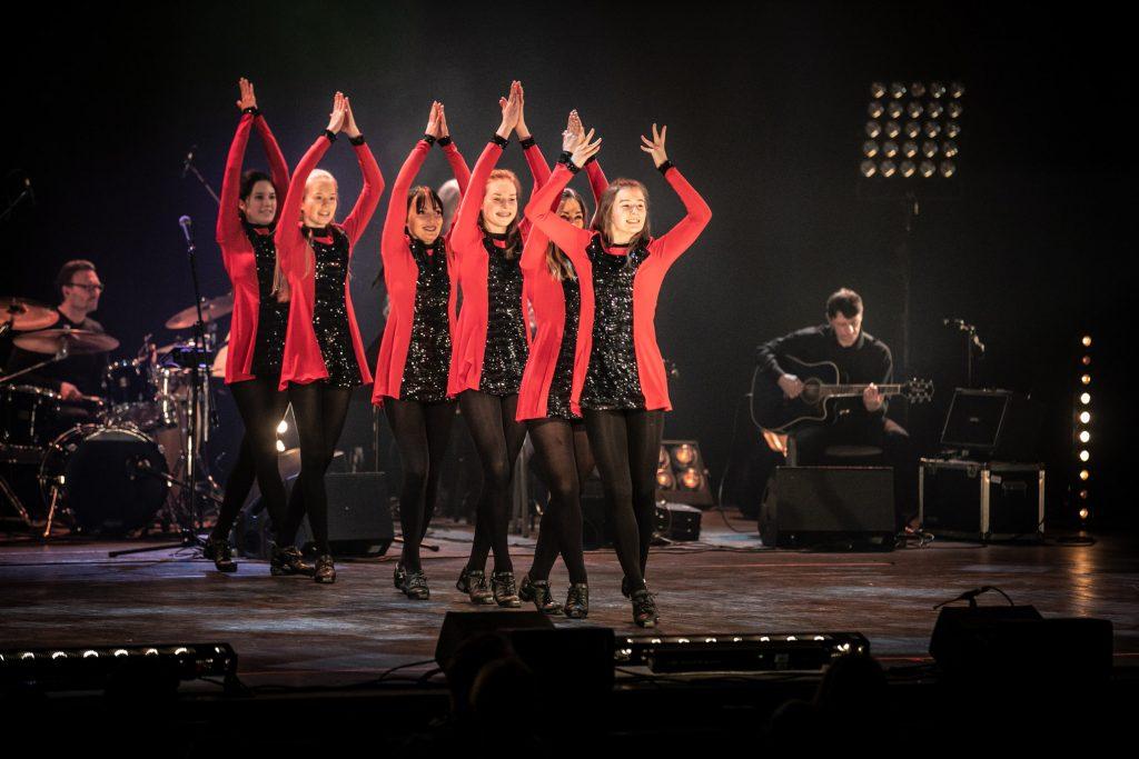 Na scenie kilka kobiet w czerwonych sukienkach w układzie tanecznym. Stoją za sobą w rzędzie z rękami uniesionymi nad głową. Za nimi gra zespół Carrantuohill.