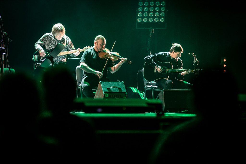 Zbliżenie na trzech muzyków zespołu Carrantuohill. Po prawej stronie siedzi mężczyzna grający na gitarze, obok mężczyzna grający na skrzypcach , lekko za nim stoi mężczyzna grający na gitarze elektrycznej.