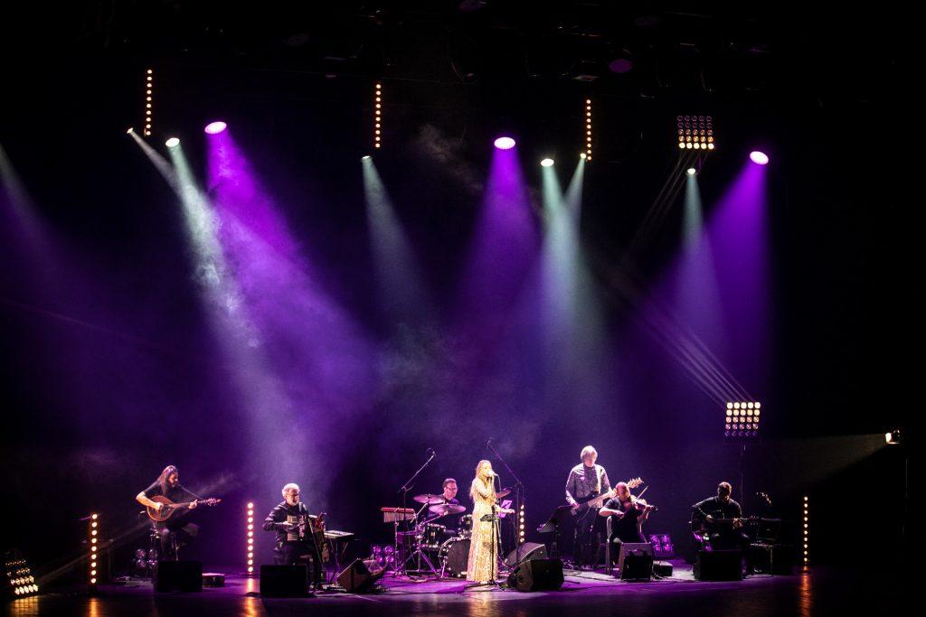 Scena oświetlona z góry smugami jasnego i fioletowego światła. Na scenie siedzi zespół muzyczny Carrantuohill. Z przodu stoi z mikrofonem kobieta w złotej, długiej sukni.