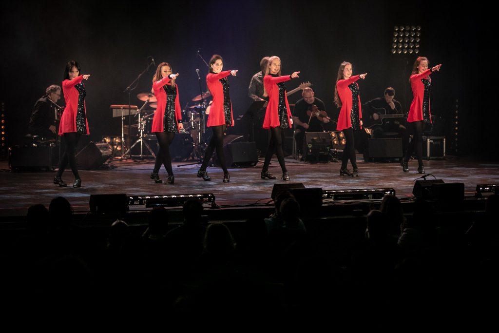 Na scenie stoi kilka kobiet w układzie tanecznym. Wzdłuż sceny w rzędzie stoją z prawymi rękami wyciągniętymi do przodu. Nogi mają skrzyżowane.
