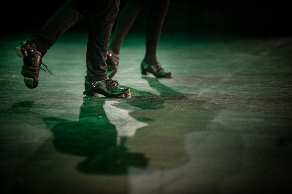 Zbliżenie na buty do stepowania dwóch osób tańczących na scenie.